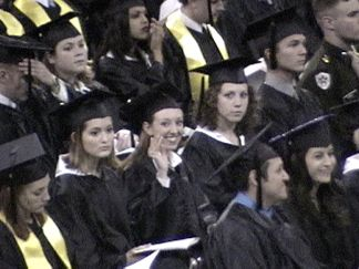 Kelly - waiving at us from her seat... She's waiting for the speech to end so she can get on with graduation!