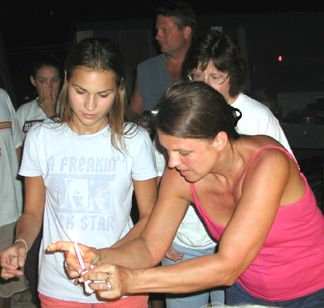 Joanie and Nicole lighting the candles on the cake