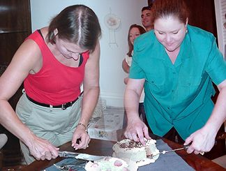 Joanie and Chandra cutting the cakes (Actually - two seperate pictures spliced together